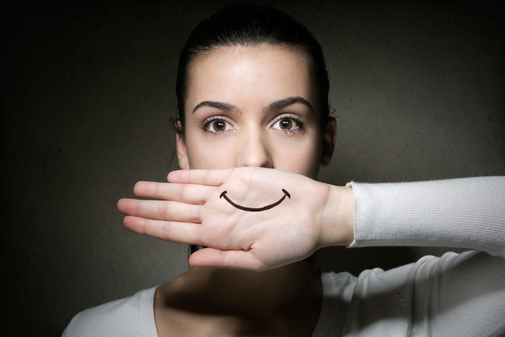 kobieta z narysowanym uśmiechem na dłoni