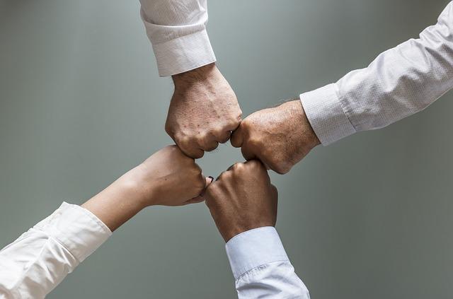 cztery dłonie złączone na znak współpracy